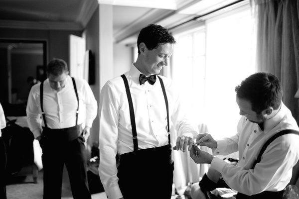 Black and white photo of men getting ready before wedding