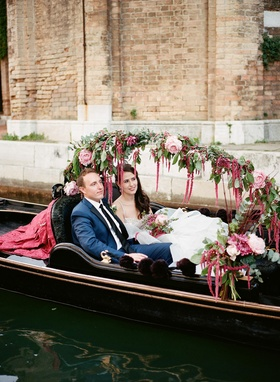 Bride in wedding dress groom in navy suit inside gondola boat Venice, Italy decorated flowers