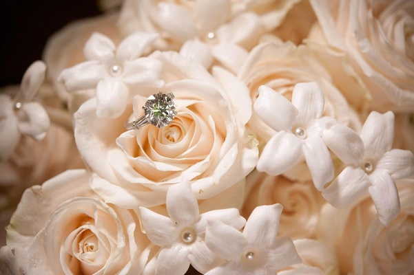 Sparkling diamond ring on peach rose and stephanotis with pearls