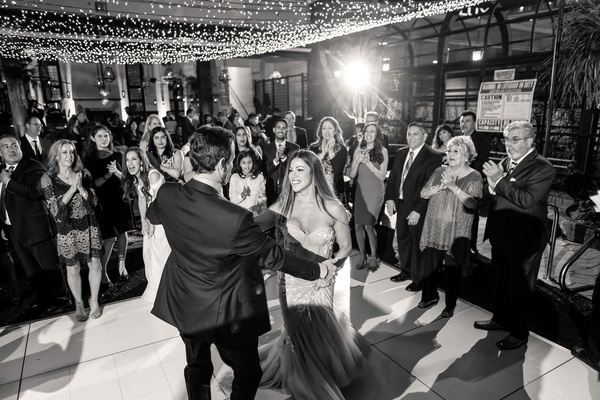 black and white photo of bride and groom dancing guests watching first dance under string lights