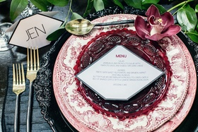 Wedding place setting with black charger, white & red floral print china, red glass plate, cymbidium