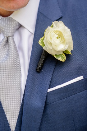Wedding ceremony groom in dark blue suit with silver tie and white ranunculus flower boutonniere