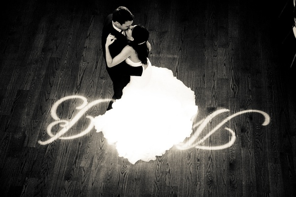 Black and white photo of bride in a Maggie Sottero dress dancing with groom