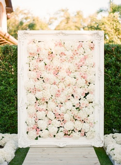Garden wedding ceremony with white frame filled with white and pink flowers at the altar