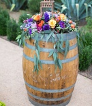 colorful floral arrangement with berry tones of pink purple orange yellow and green on wine barrel