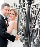 Groom hugs bride in strapless Reem Acra wedding dress