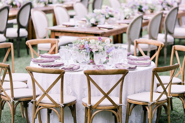 wedding reception outdoor hawaii venue light purple linen wood vineyard chair low flower arrangement