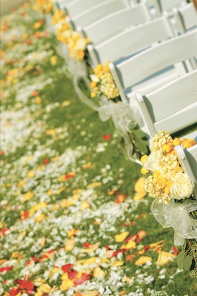 yellow flowers and roses petals decorate aisle