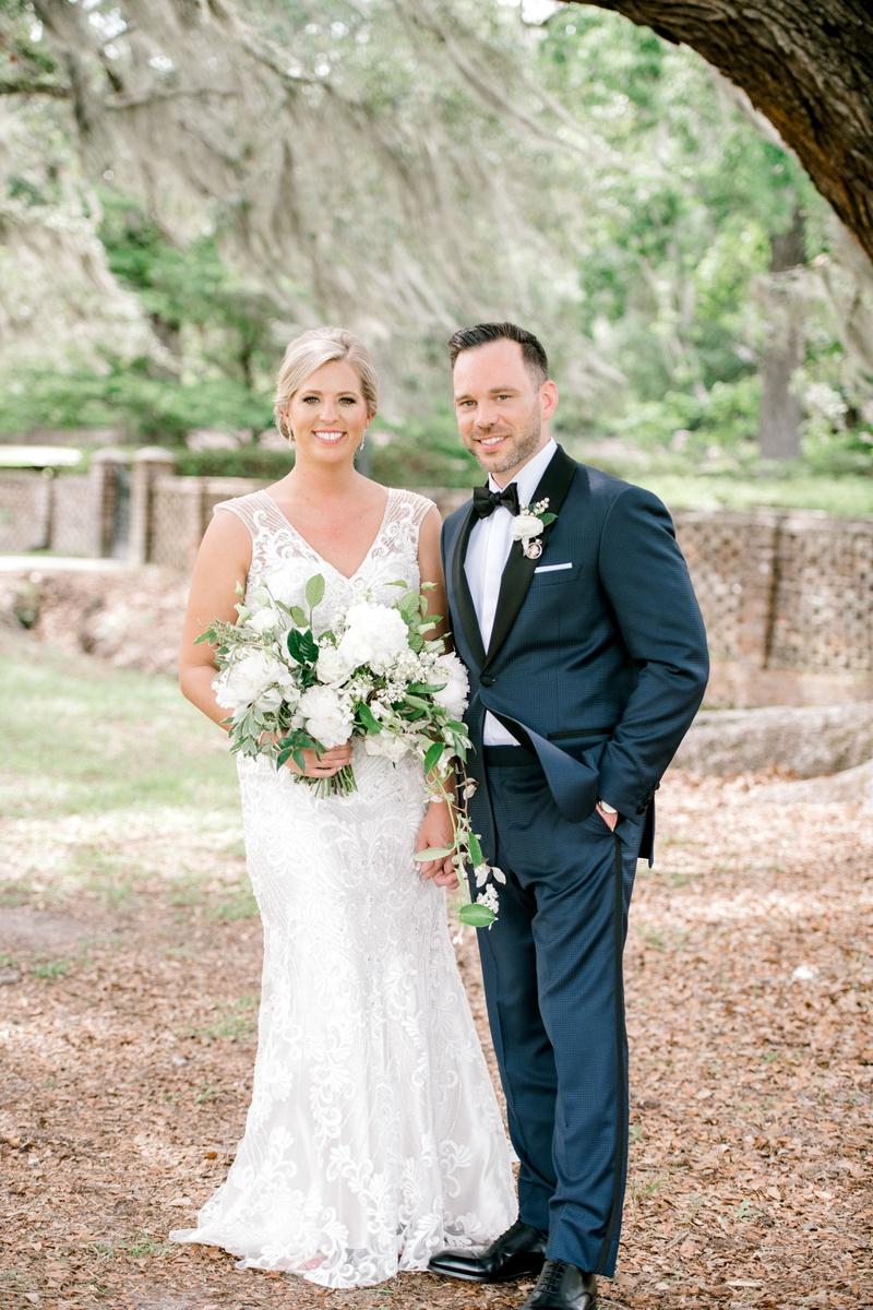 bride in v neck embroidered wedding dress sleeveless groom in navy blue suit black lapel tuxedo tie