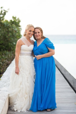 Bride with mother of bride in blue dress on pier