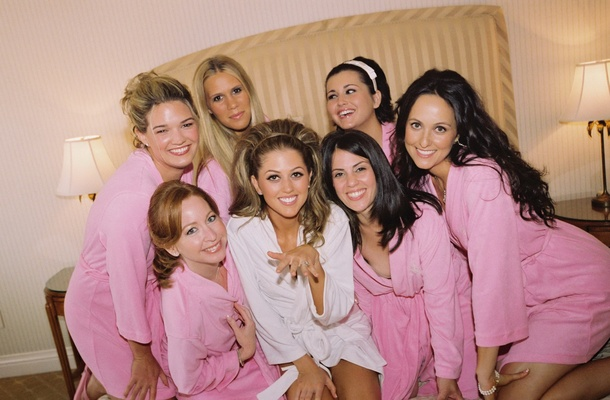 Bride in white robe with six bridesmaids in bridal suite