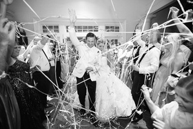 Black and white photo of bride and groom leaving wedding through tunnel of friends with confetti