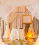 draped white ceremony chuppah with floral arrangements of white flowers and greenery