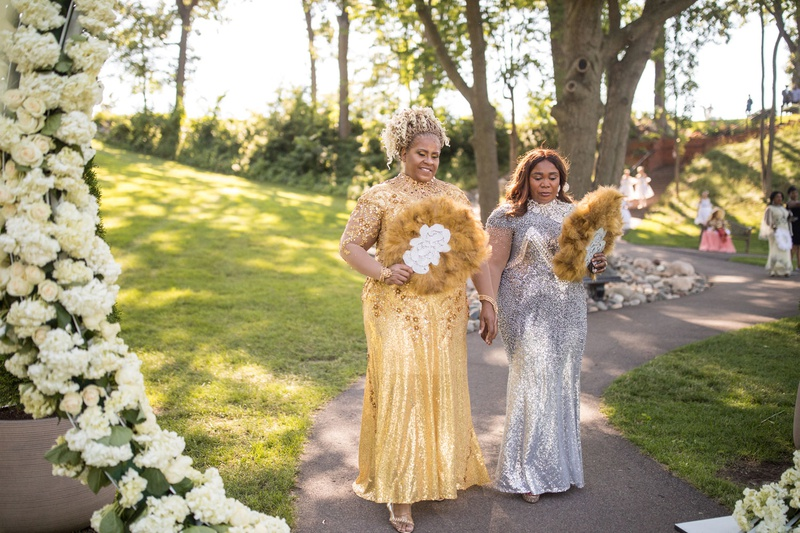 mother of bride and mother of groom in gold and silver sequin gowns feather fans outdoor ceremony