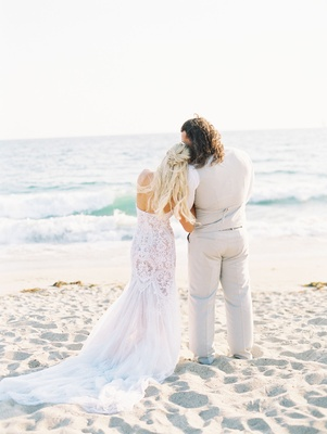 Lana and Rusev wedding day looking out to ocean from beach wedding lace dress tan suit vest