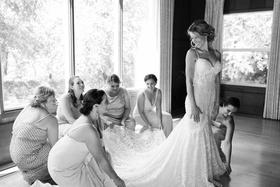 black and white photo bridesmaids helping bride berta wedding dress ready