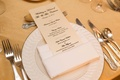 champagne colored menus on white plates on gold table linens