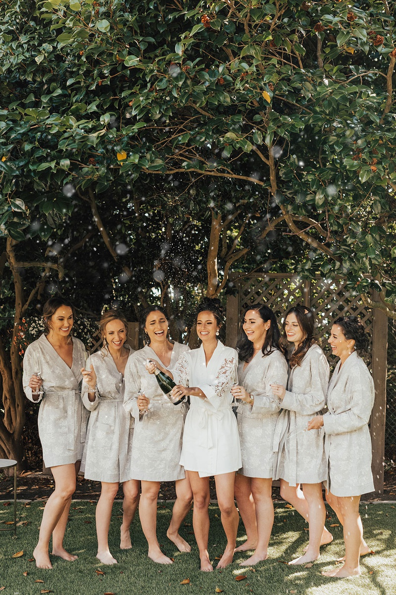 bridesmaids in greey robes bride in lace sleeeve robe popping champagne seattle wedding