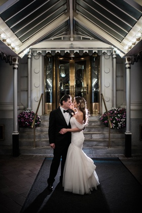 newlyweds pose in front of hotel venue, bride in monique lhuillier mermaid off-the-shoulder sleeves