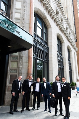 Groom and groomsmen in New York City in tuxedos in front of hotel city wedding