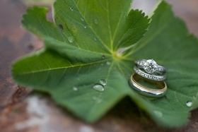 Bride's solitaire Tiffany & Co. engagement ring and diamond wedding band on green leaf in Montana