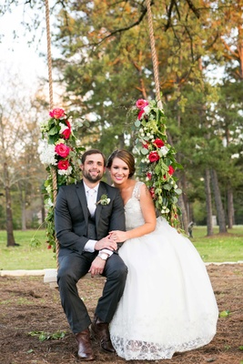 Bride in Nardos Iman wedding dress with groom on rope swing decorated with flowers and garlands