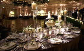 Floral and foliage chandeliers with candles and tall candlesticks ivory flowers on tables live band