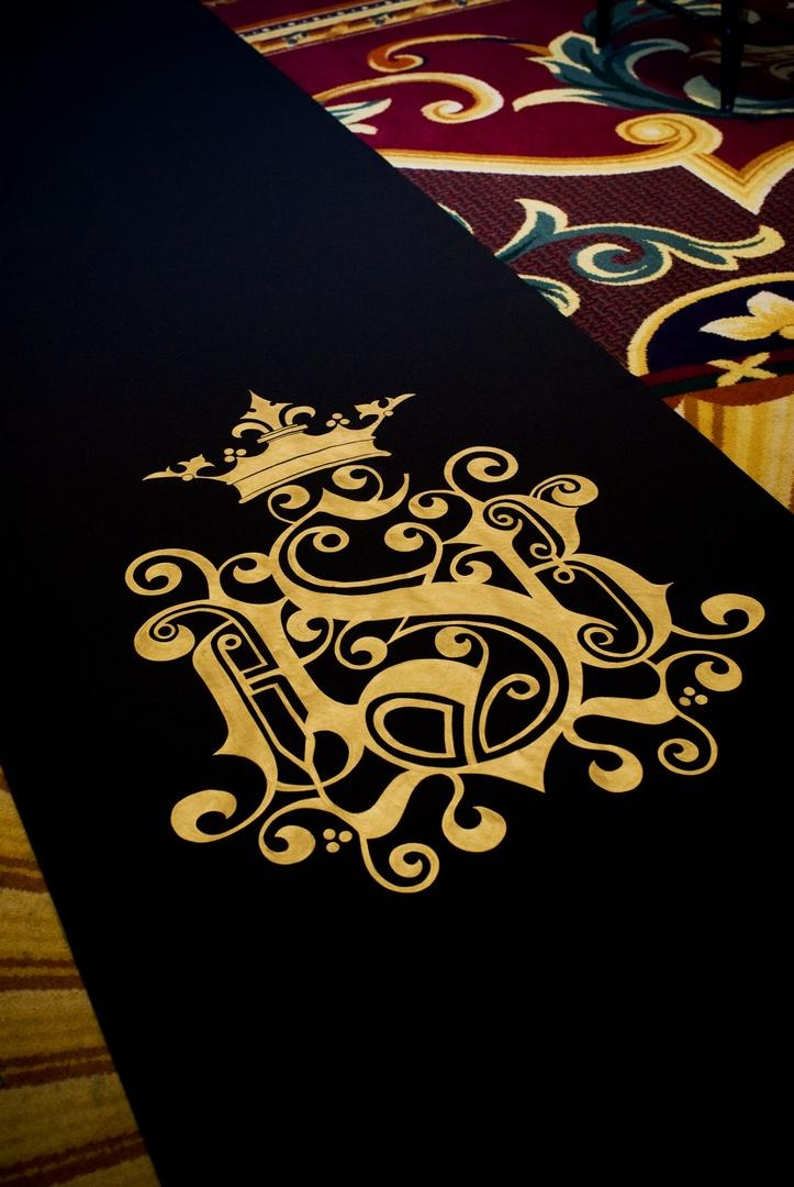 Black aisle runner with gold monogram design by The Original Runner Company for a wedding