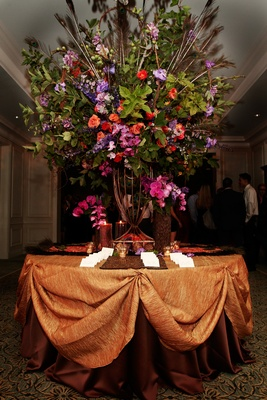 large arrangement with greenery, peacock feathers, and pink, orange, purple, and red flowers.
