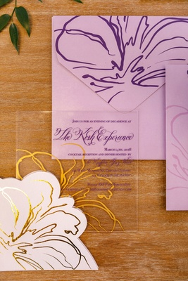 Purple lettering gold flower purple envelope see through clear lucite acrylic invite on wood table
