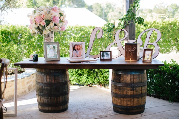 guest book table with barrel base, rustic wooden initials painted white, framed photos