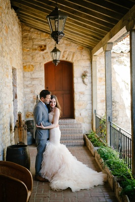 bride in blush ruffled mermaid dress, groom in grey suit, hug during first look