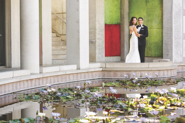 Bride and groom embrace next to pond filled with flowers