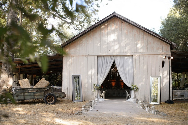 Entrance to barn wedding with lanterns and mirrors