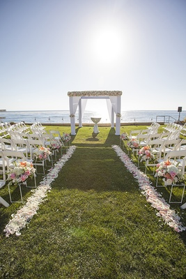 Grass lawn oceanfront outdoor ceremony with white drapery and flower chuppah and flower petals aisle