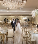 wedding reception portrait of bride and groom crystal chandelier gold white pink decor