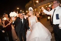 Bride and groom in NYE accessories leave wedding