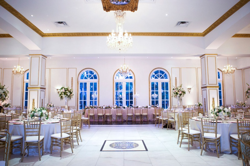 Room shot of wedding reception in chateau ballroom chandelier pink long table and round tables dance