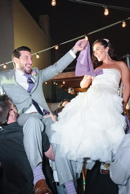 Bride in a fit-and-flare Vera Wang dress, ruffled skirt and groom in grey suit, purple tie, socks