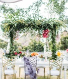 wedding reception white table gold chairs purple chair cover overhead greenery centerpiece pink