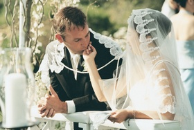 Bride and groom taking part in mantilla veil and cording ritual