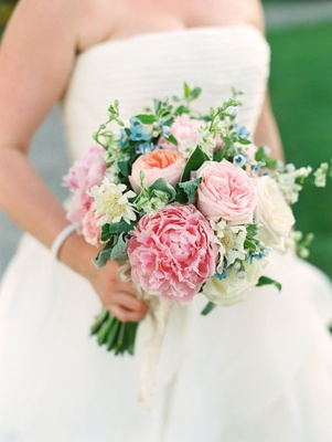 Bride in strapless wedding dress holding bouquet pink peony garden rose peach blue flower greenery