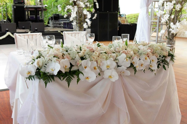 Wedding reception sweetheart table is covered with pale pink and white fabric and flowers