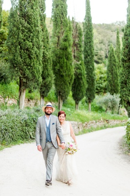 bride in wedding dress with bouquet groom in casual suit with hat italy destination wedding umbria