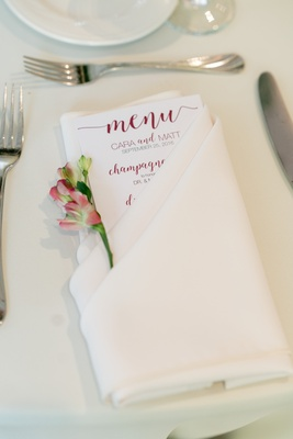 menu with burgundy calligraphy tucked into cream linen with a blossom