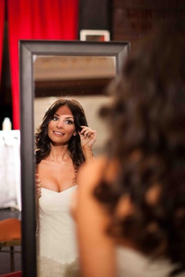 Bride looking in mirror on wedding day with hair down