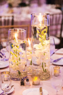 submerged orchids with floating candles as centerpieces at wedding reception