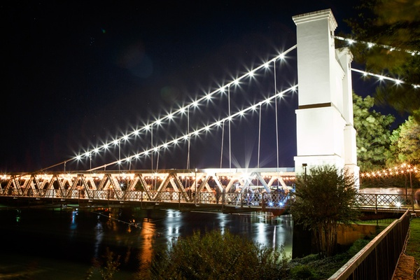 wedding reception at waco suspension bridge with lots of lights over river
