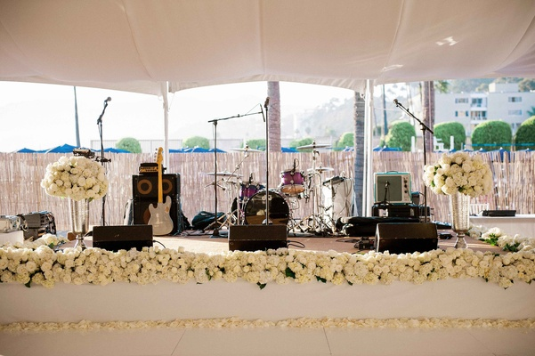 Beach tented wedding reception with a raised stage, band's intruments, white roses, hydrangeas