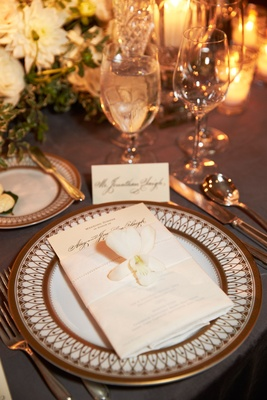 Ornate wedding charger plate with menu and belly band with white orchid and low centerpieces
